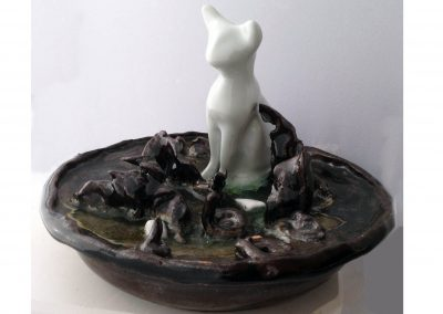 """A curious Litter"" A pristine white porcelain cat looks very out of place in a muddy puddle with gooey worm critters crawling around at its feet.  You can take the meaning of the word ""litter"" either way. 7""x6"""