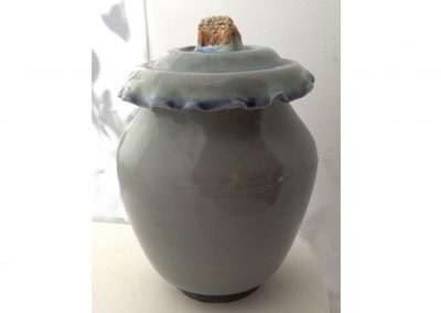 """The Scream The blue celadon jar represents the rising ocean.  The knob is a sinking house with a drowning man. 5""""x7"""" Porcelain"""
