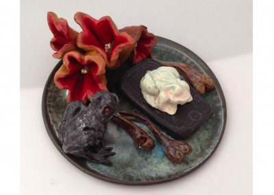 """Pierre's Experiment"" Science has produced two headed tadpoles.  Here the tadpoles are the product of a toad and a red eyed frog enjoying an old cell-phone as part of their homey environment graced with a nice bloom of Alien Botanicals. 6"" x 4"" Earthenware"
